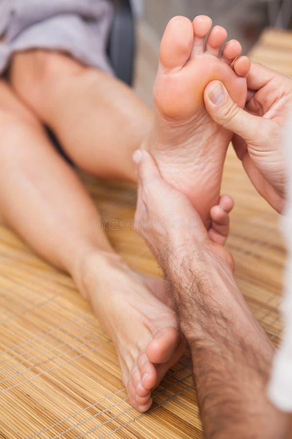Pedicure die een klantenvoet masseren stock foto's