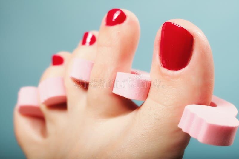 Pedicure do pé que aplica as unhas do pé vermelhas no azul fotos de stock royalty free
