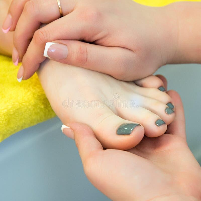 Pedicure och fotmassage Kvinna i en skönhetsalong för pedikyr- och fotmassage royaltyfri bild