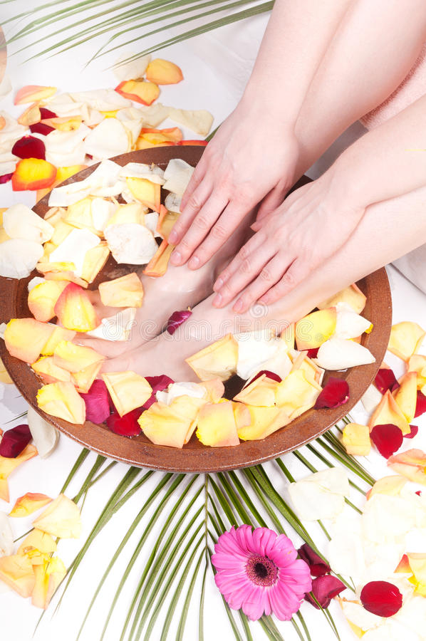 Pedicure'u i manicure'u zdrój z płatkami i kwiatami zdjęcie royalty free