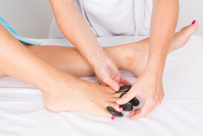 Pedicurebehandeling bij een kuuroord of een schoonheidssalon met de pedicure die de zolen van haar voeten met zwarte hete steen m stock afbeelding