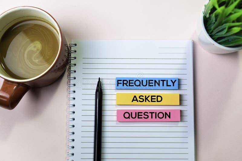 Pedido con frecuencia pregunte el texto del FAQ en notas pegajosas con concepto del escritorio de oficina fotos de archivo