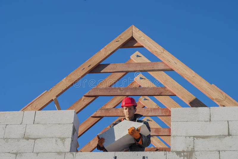 Pediment of aerated concrete. Master mason holding a large block of aerated concrete stock images