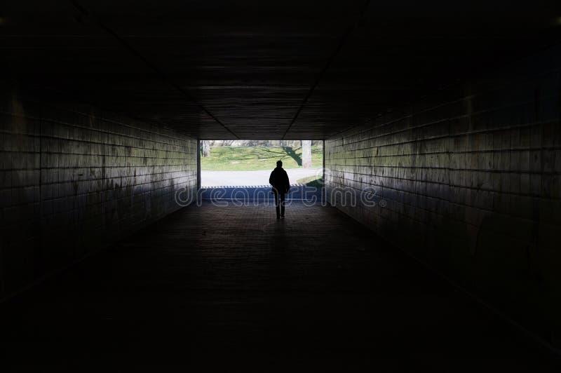 Pedone che cammina tramite il tunnel scuro fotografie stock libere da diritti