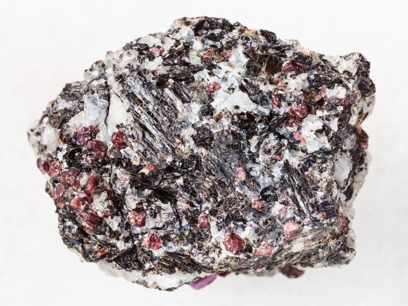 pedra áspera do gneisse com os cristais do corindo no branco foto de stock