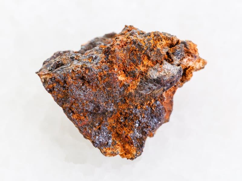 pedra áspera do hematita (minério de ferro) no mármore branco imagem de stock