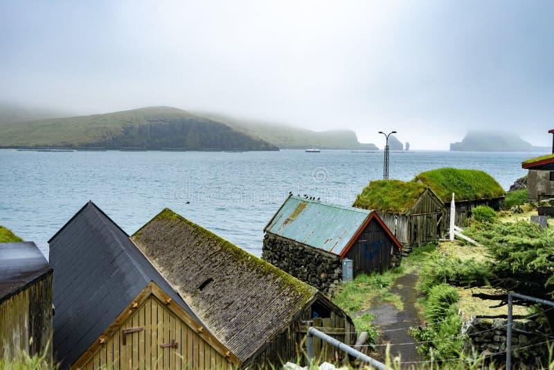 Pedra bonita e grama verde das casas de madeira no telhado, no lado de mar ao lado do oceano azul e no Drangarnir no fundo nevoen imagem de stock