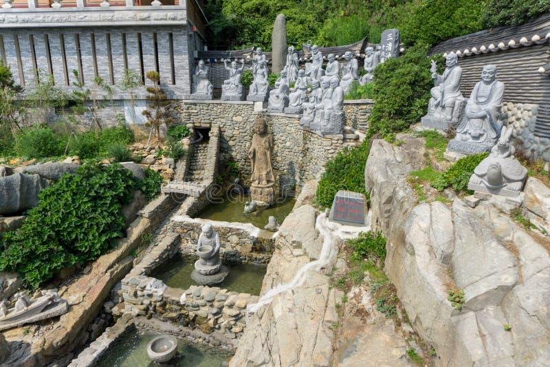 A pedra branca cinzelou estátuas da Buda chinesa, dos padres e dos muitos animais na cachoeira artificial no templo de Haedong Yo fotografia de stock