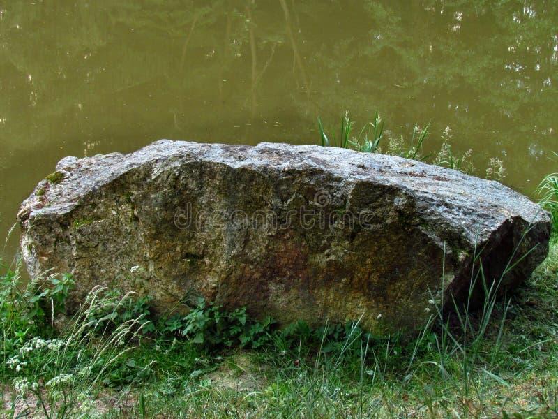 Pedra grande na grama pelo rio fotografia de stock