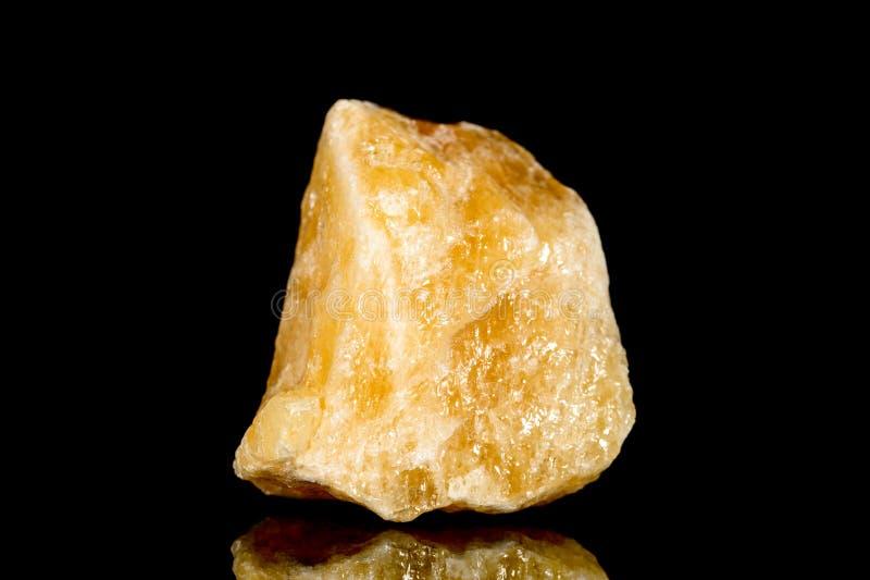 Pedra mineral da calcite alaranjada crua na frente do fundo preto imagens de stock