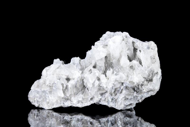 Pedra mineral da calcite branca crua na frente do fundo preto imagem de stock royalty free