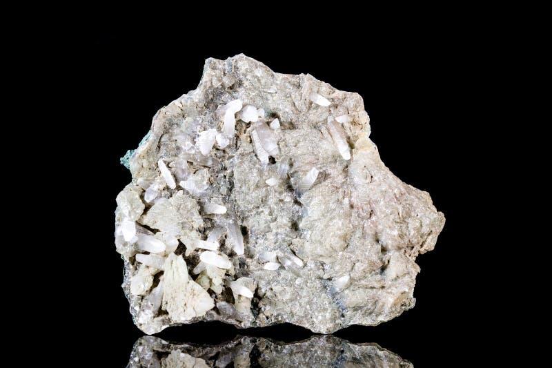 Pedra mineral de quartzo branco cru na matriz na frente do fundo preto imagem de stock royalty free