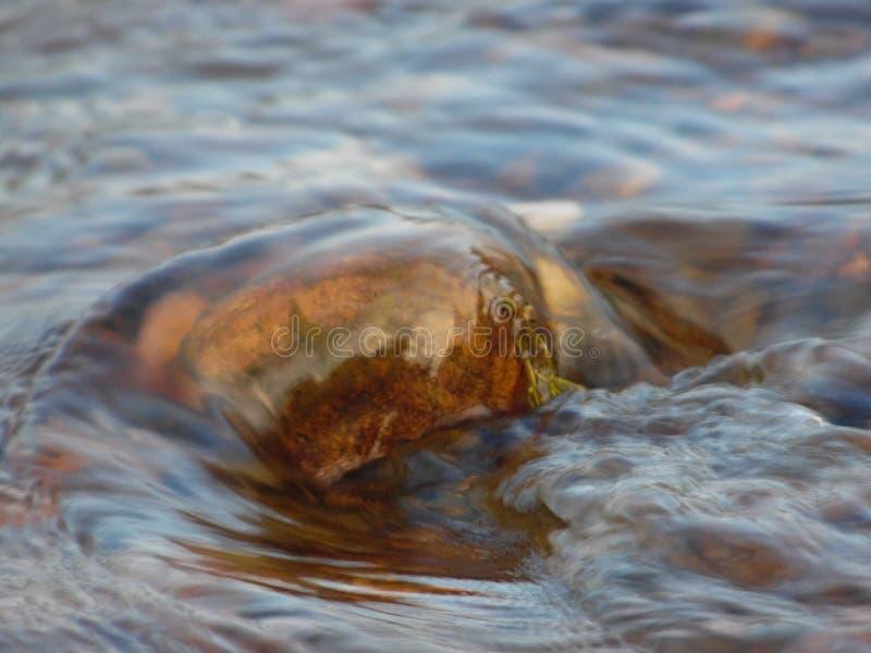 A pedra na água foto de stock