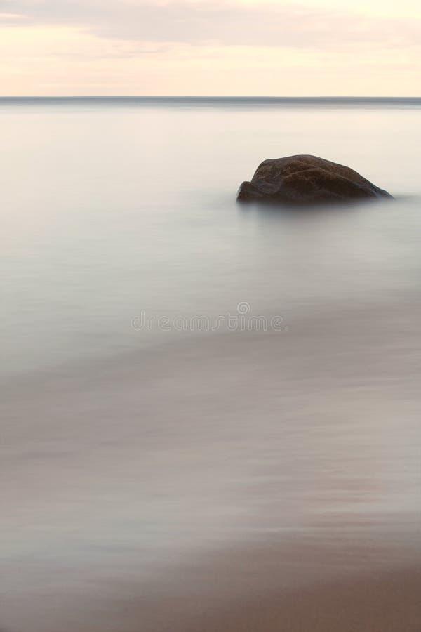 Pedra na água macia com céu fotografia de stock