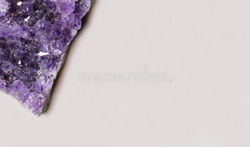 Pedra preciosa violeta semipreciosa cura bonita da ametista no fim branco do macro do fundo acima com espaço da cópia foto de stock