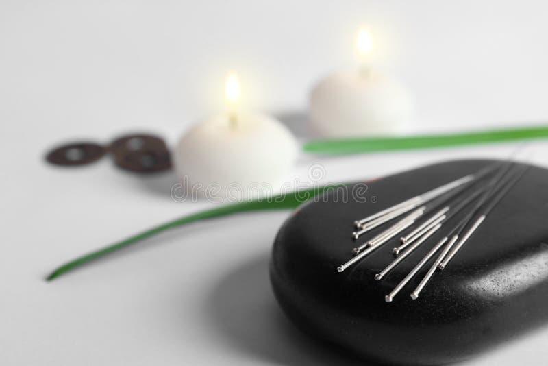 Pedra preta dos termas com grupo de agulhas da acupuntura fotografia de stock