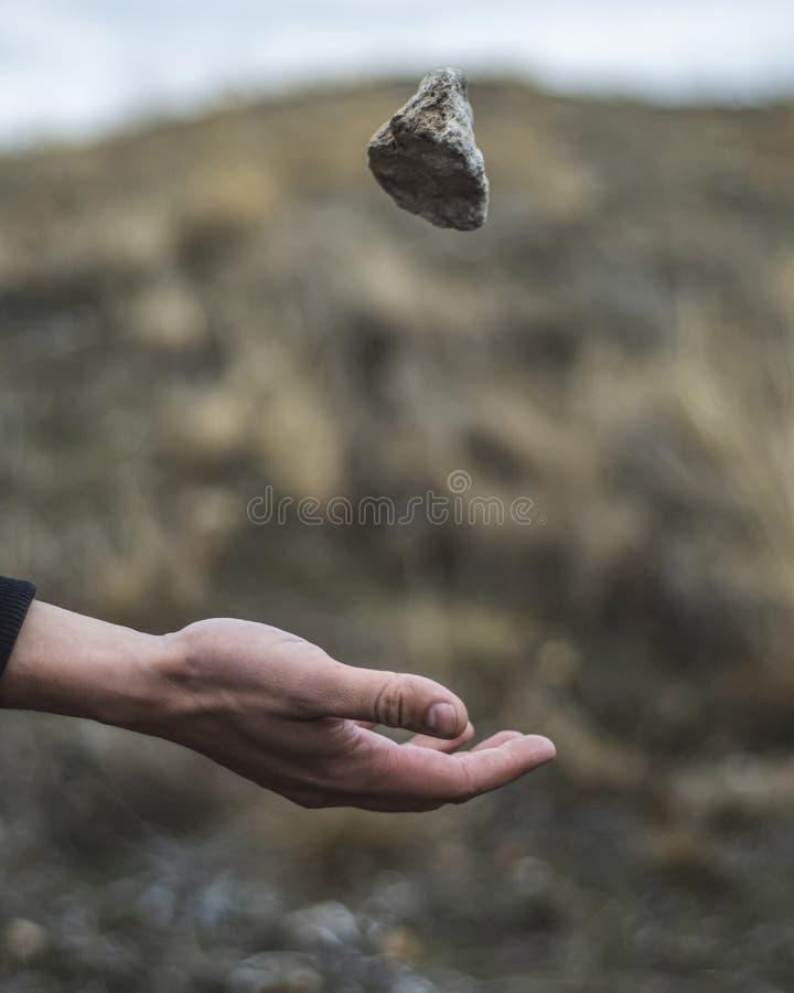 Pedra que paira sobre o braço Uma pedra jogada no ar gravidade fotografia de stock royalty free