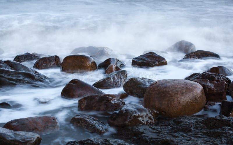 Pedra redonda na onda do mar fotos de stock royalty free