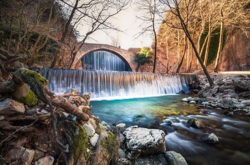 A pedra velha de Paleokarya arqueou uma ponte entre duas cachoeiras Prefeitura de Trikala, Grécia imagens de stock royalty free