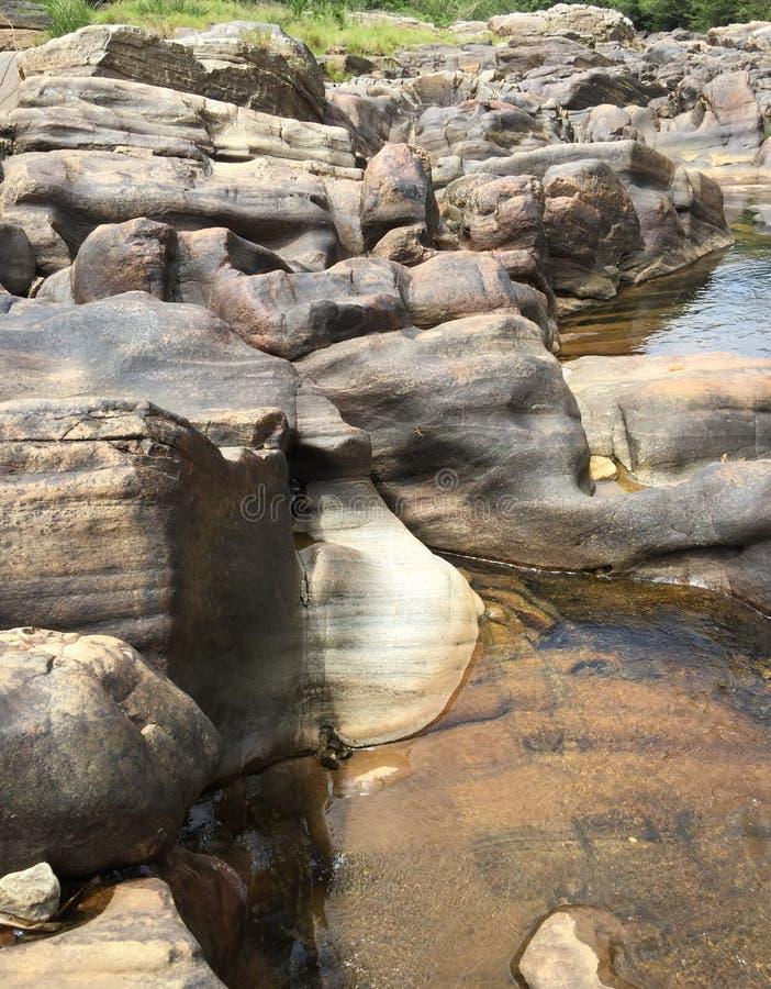 Pedras através para fora do lado do rio imagens de stock