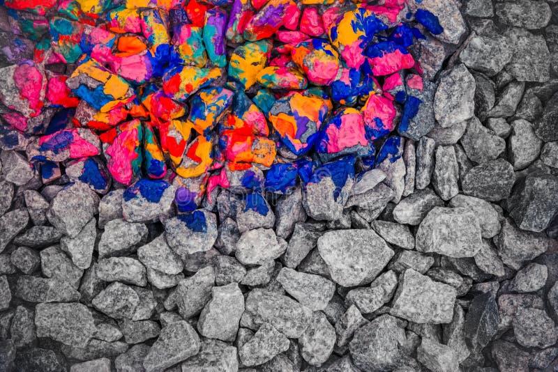 Pedras coloridas na tinta diferente da cor em um meio, a segunda metade - pedras cinzentas monocromáticas foto de stock