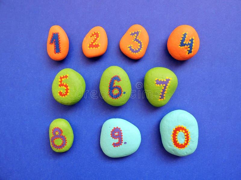 Pedras com números da pintura fotos de stock