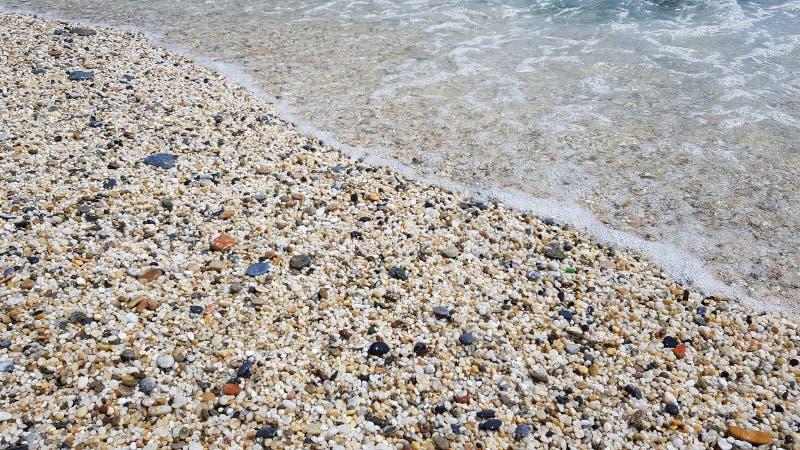 Pedras da praia e onda do oceano imagens de stock