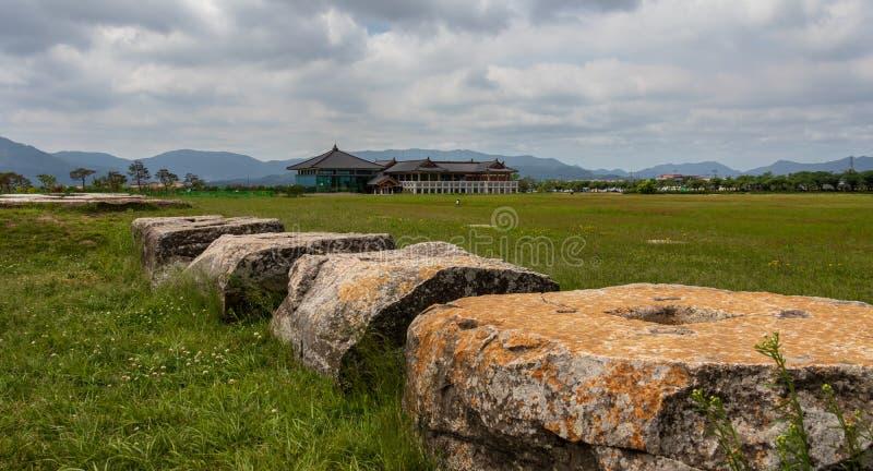 Pedras da ruína do local do templo de Hwangnyongsa com o centro da cultura da história no fundo Gyeongju, Coreia do Sul, ?sia imagem de stock royalty free
