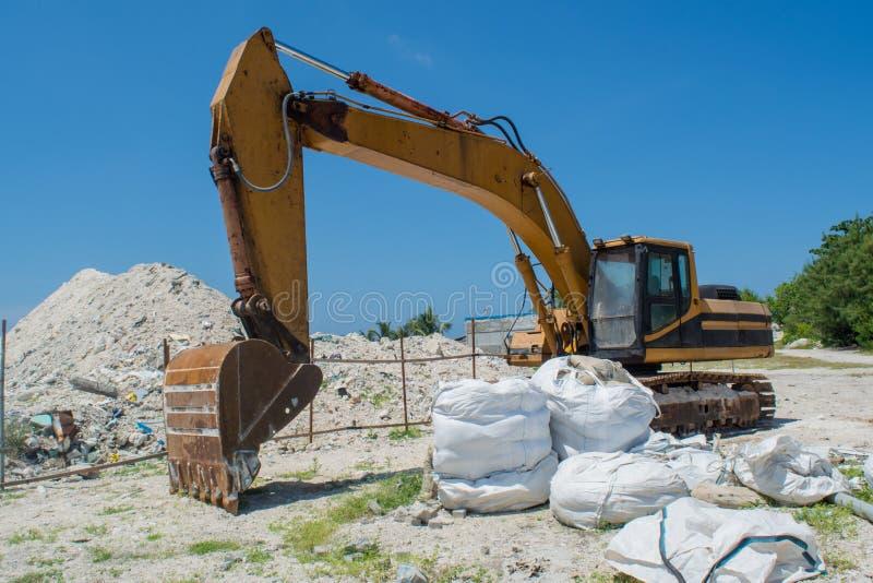 Pedras de escavação da draga amarela na ilha tropical Villingili imagens de stock