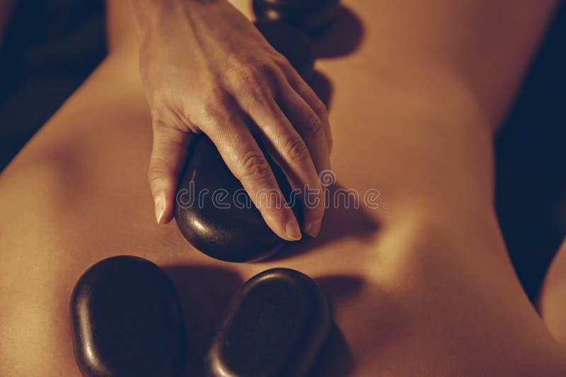 Pedras de Placing Hot do massagista na parte traseira de uma mulher foto de stock