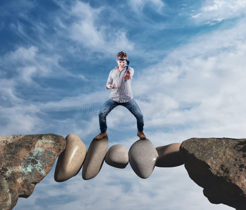 Pedras do desafio Homem de negócios na posição da posição de batalha em rochas no meio imagens de stock royalty free