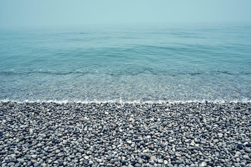Pedras do seixo em um fundo da costa de mar foto de stock