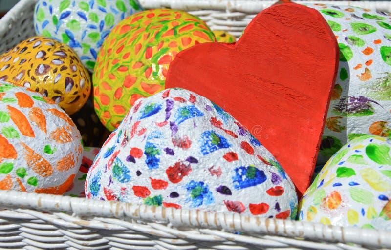 Pedras e coração pintados coloridos do amor na cesta branca fotografia de stock royalty free