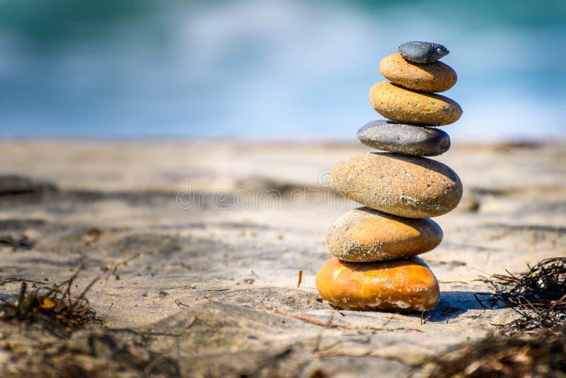 Pedras empilhadas equilibradas naturalmente na areia fotografia de stock