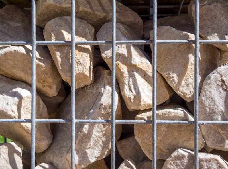 Pedras, fixadas por uma grade do metal contra o rastejamento imagens de stock