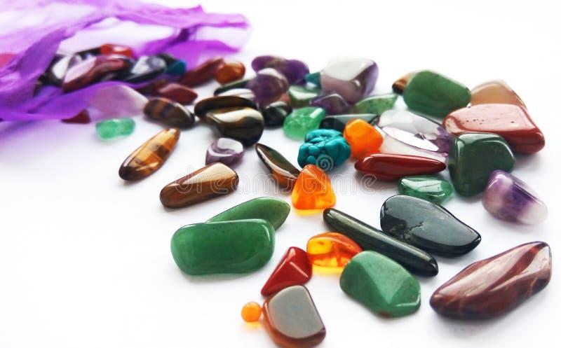 Pedras preciosas e gemas semi preciosas coloridas brilhantes naturais com um saco no fundo branco fotos de stock royalty free