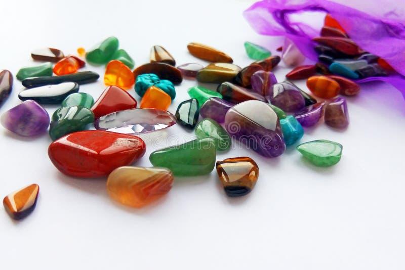 Pedras preciosas e gemas semi preciosas coloridas brilhantes naturais com um saco no fundo branco foto de stock royalty free