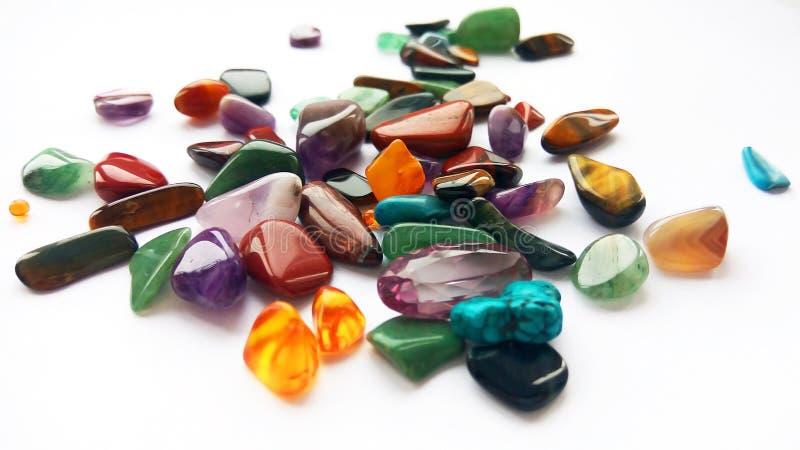 Pedras preciosas e gemas semi preciosas coloridas brilhantes naturais no fundo branco imagem de stock