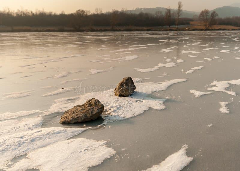 Pedras que encontram-se no rio congelado com os pontos da neve fraca imagens de stock