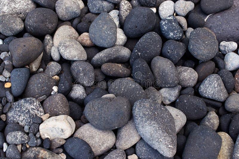 Pedras redondas escuras de Vulcanic na costa dos ísquios, Itália imagem de stock