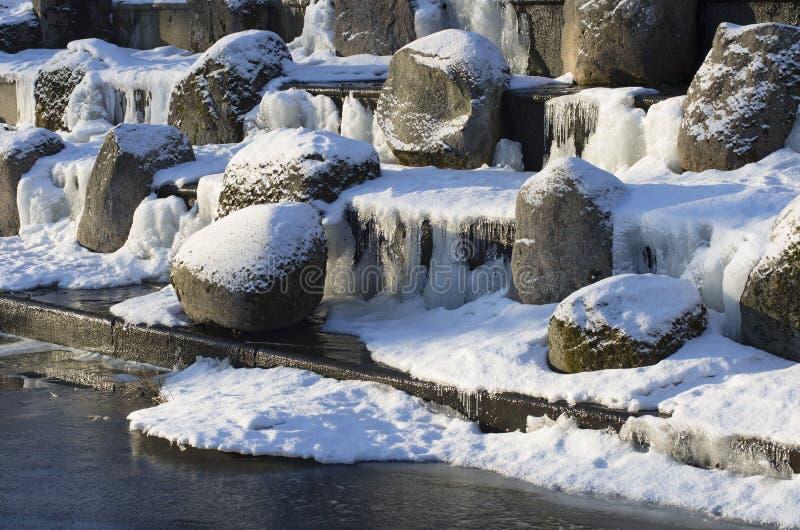 Pedregulhos cobertos de neve na cascata do granito imagem de stock