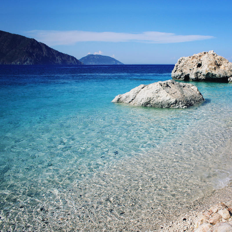 Pedregulhos enormes Costa rochosa Praia pequena Mar azul imagem de stock royalty free