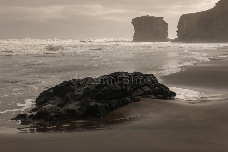 Pedregulhos vulcânicos na praia de Muriwai foto de stock