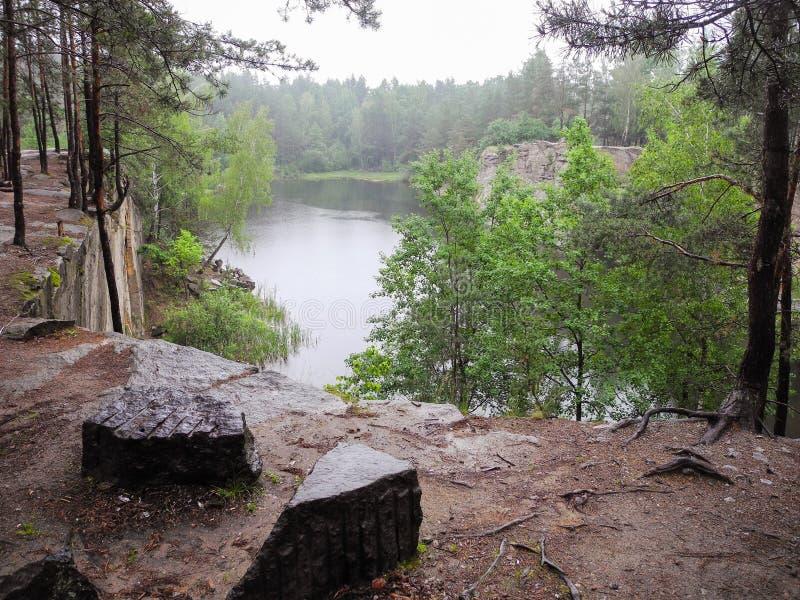 Pedreira inundada abandonada no lago da floresta nos afloramento Geological da floresta foto de stock royalty free
