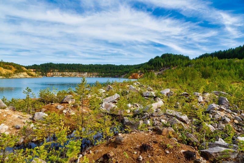 Pedreira inundada para a extração do granito com a rocha no primeiro plano e da água azul com picos no fundo fotos de stock