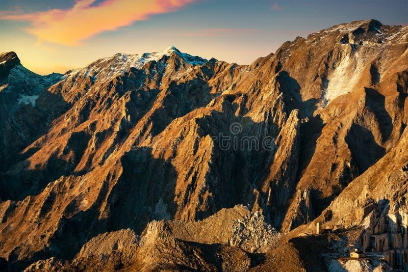 Pedreira nevado do montanha do alpi de Apuane e a de mármore no por do sol no winte foto de stock royalty free