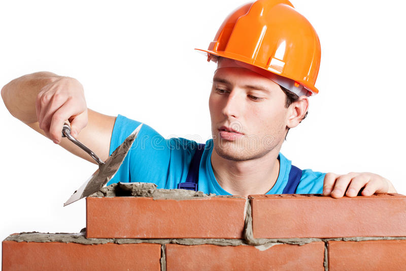 Pedreiro da construção que instala o tijolo vermelho imagens de stock