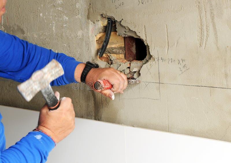 Pedreiro que prepara o furo na parede para colocar tomadas elétricas de uma caixa para a renovação da casa foto de stock
