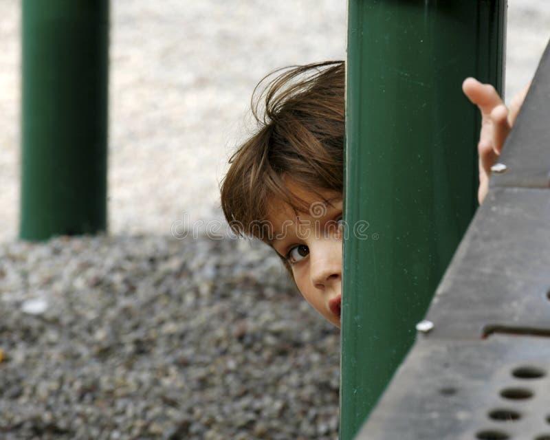 Peek. Young girl peeking around post of playground equipment stock photo
