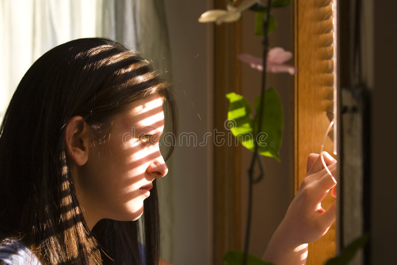 Peek. Young female teen peeking through window blinds royalty free stock photos
